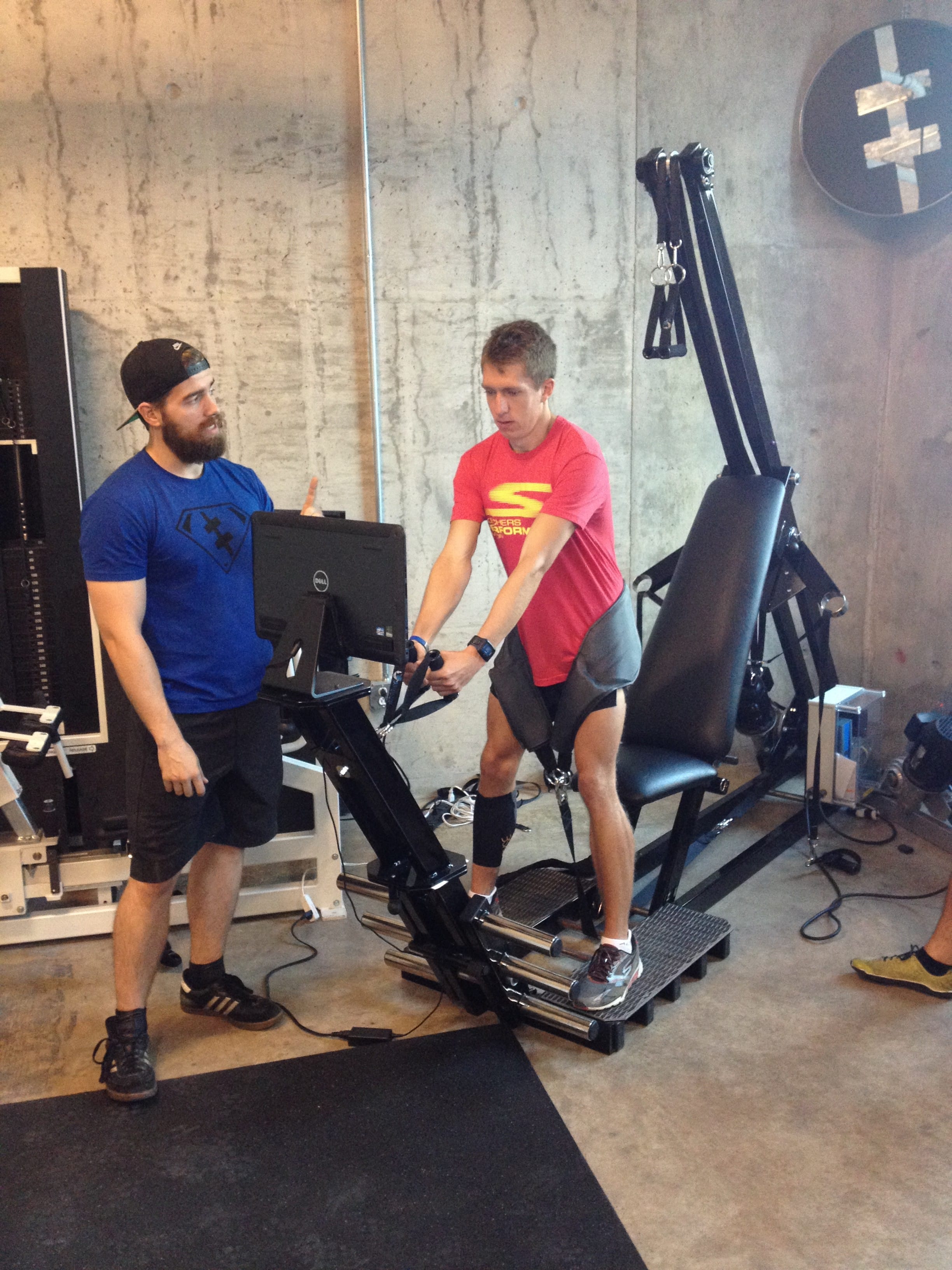 Bo Alexander (L) instructs Shane Niksic on how to read the data display while performing belt squats with the ARX machine.